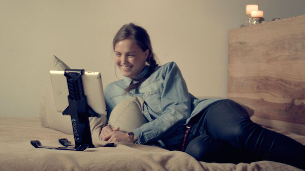 Woman reclining on bed Skyping with tstand in desktop mode